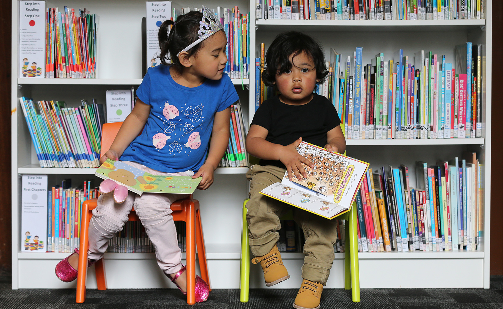 Two children sitting in front of a book case and looking at books
