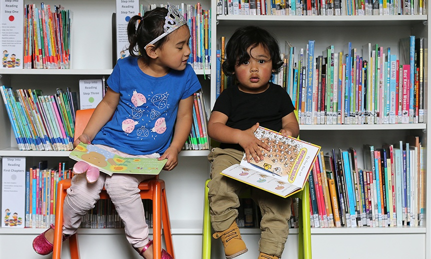 Two children reading the books sitting in front of a bookcase
