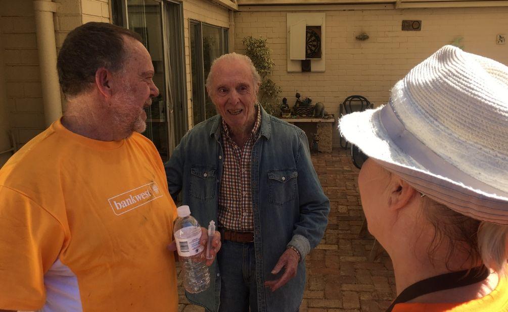 Three men talking one wearing a bankwest tshirt