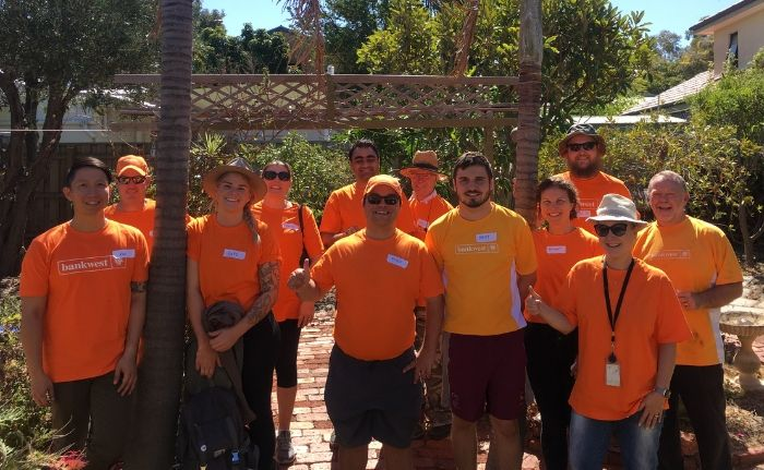 People with Bankwest tshirts in the backyard of Don helping out