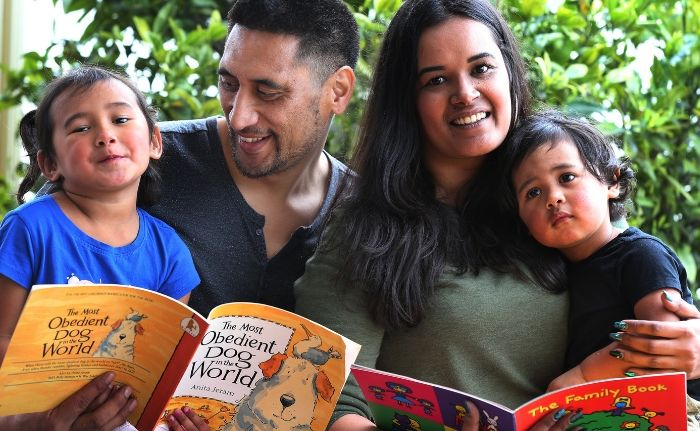 Parents with two children reading two books in their hand