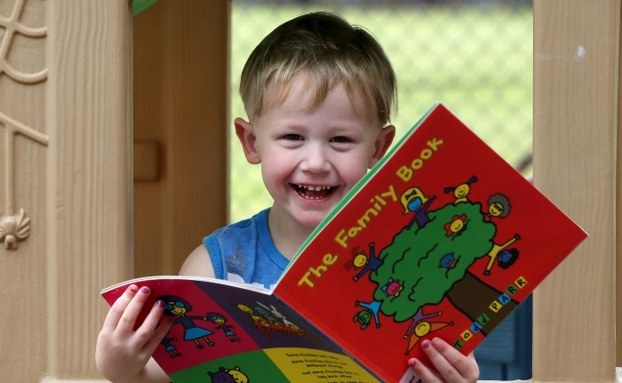 A 2 year old boy looking at a book called ' The Family book'