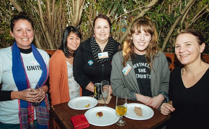 Five women smiling and dining at the 54 Connect Community Garden