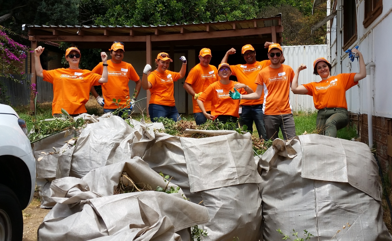 People with bankwest tshirts on cleaning up gardening